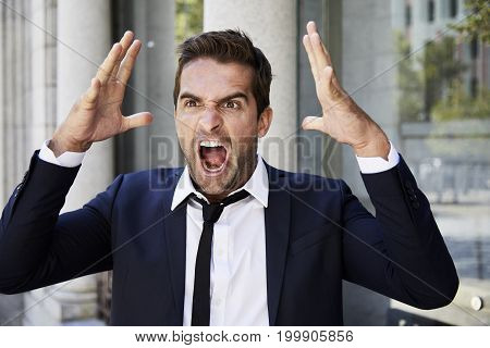 Angry businessman in suit shouting in rage