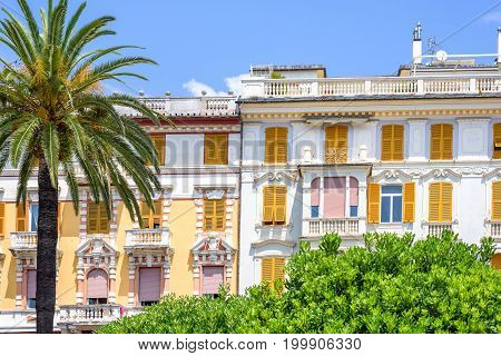 Beautiful daylight view to white and yellow hotel on little green trees background. Rapallo, Italy
