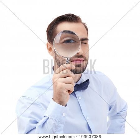 Handsome young man with magnifier on white background