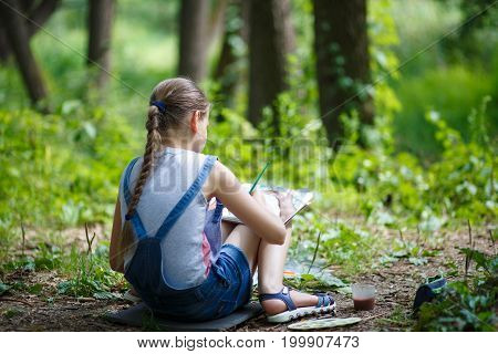 Girl Painter Paints Trees In The Park.