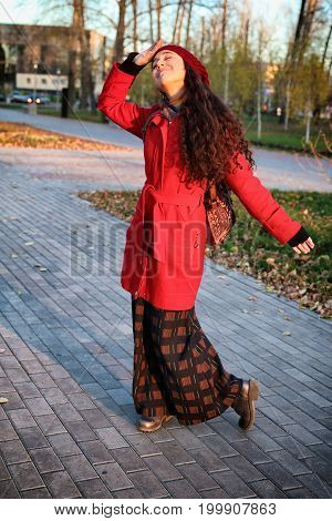 attractive young woman in red coat enjoying autumn sun.