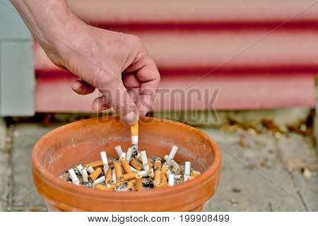 Cigarette is expressed in an ashtray with many Cigarette butts