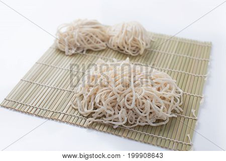 close up of raw egg noodles on bamboo