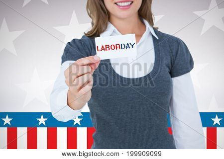 Smiling woman showing card  against digitally generated image of stage