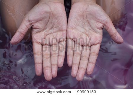 withered hands of young girl after swimming is long time