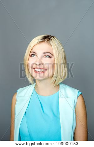 Smiling girl looking up at empty gray background