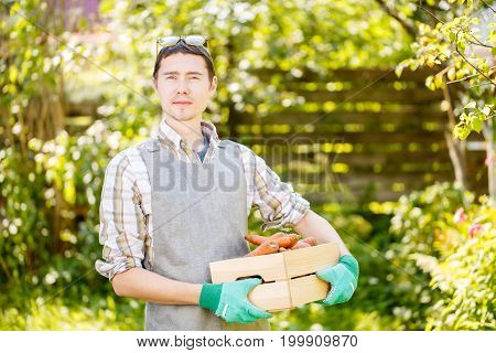 Photo of man in gloves holding box of carrots in hands