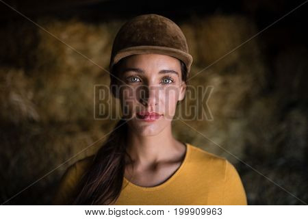 Portrait of serious female jockey standing against hay in stable