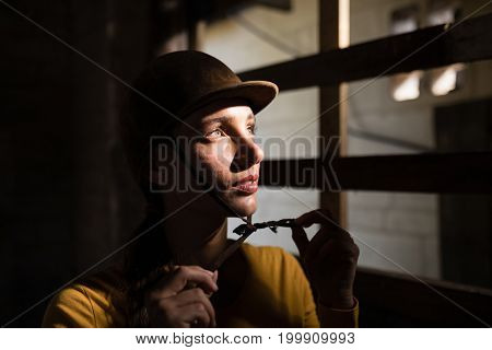 Thoughtful female jockey looking away while standing in stable