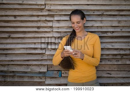 Female jockey using smart phone while standing by stable