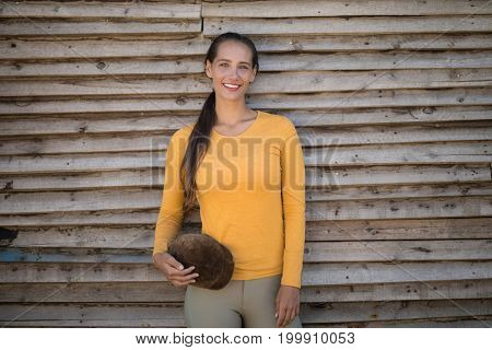 Portrait of happy young jockey standing by wooden wall