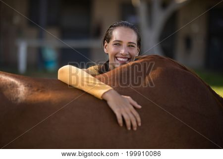 Portrait of smiling female jockey leaning on horse at barn