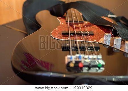 Closeup image of dark brown electric bass guitar