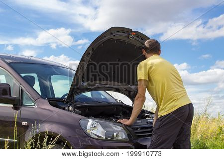 In the summer a car was broken by a man near the open hood of a car