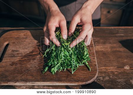 Cropped Shot Of Man Sorting Ruccola Leaves On Cutting Board