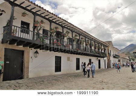 Colonial house with balcony with clouds and people