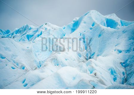 The blue glacier rises and shines in the daylight. The slopes of the blue glacier in the sunlight. Dirty stains on the slope of the glacier. Beautiful blue glacier against the sky. Uneven surface of the glacier in the sun.