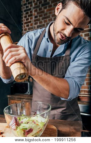 Handsome Young Man Adding Pepper With Mill Into Salad