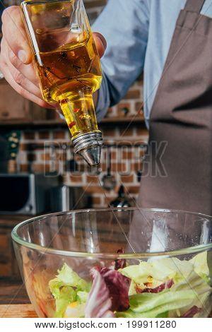 Close-up Shot Of Man Adding Olive Oil Into Salad