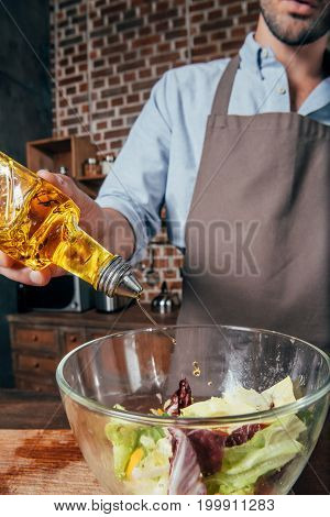 Close-up Shot Of Handsome Young Man Adding Olive Oil Into Salad
