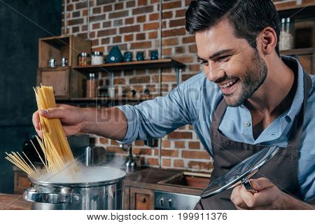 Smiling Young Man With Apron Cooking Pasta