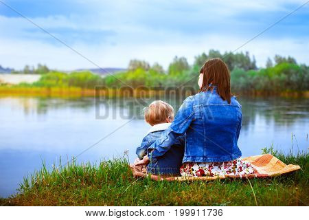 Mother hugging her little son on the bank of the river