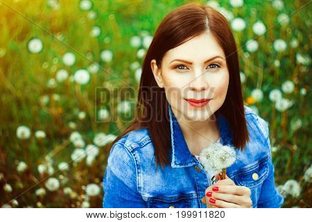 Beautiful young woman among dandelions and grass