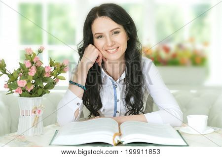 Portrait of a young woman reading interesting big book