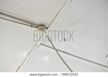 Smoke detector of fire alarm on white wooden ceiling. White