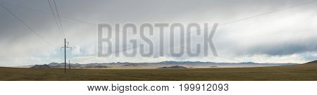 Electric power transmission pylons on inner mongolia grassland at sunrise