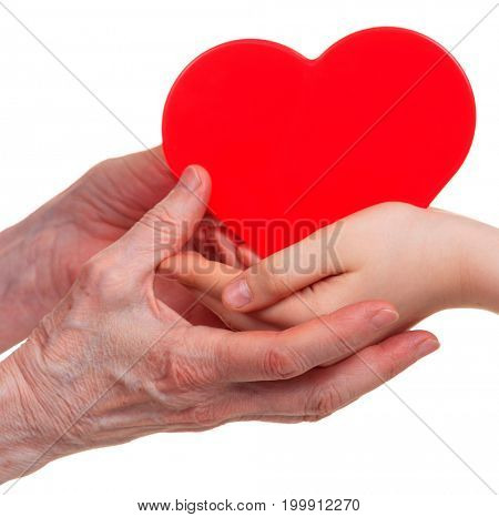 Old and young hands holding red heart, isolated on a white background.