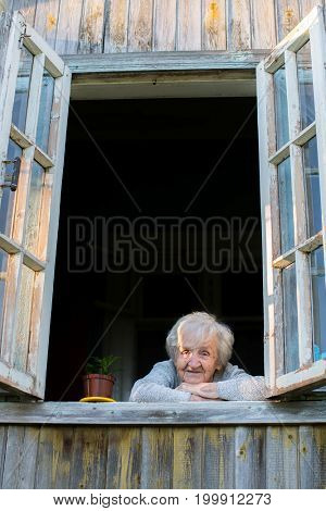 Elderly woman, a grandmother, looks from window of a village house.