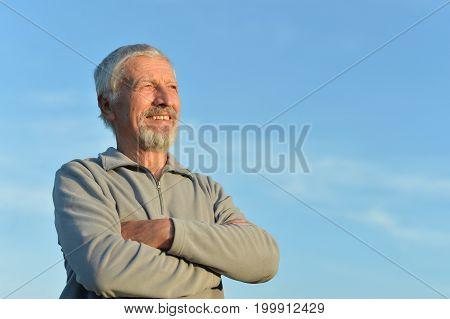 Portrait of senior man against blue sky