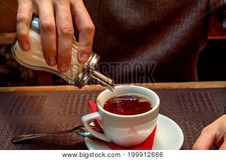 Sugar consumption concept hand adding white sugar to tea in cup