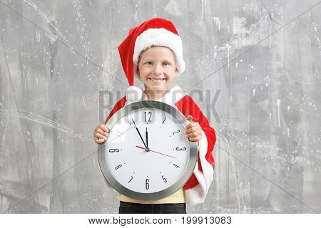 Cute little girl in Santa Claus suit with clock on grunge background. Christmas countdown concept