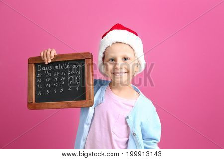 Cute little girl in Santa hat with chalkboard counting days until Christmas, on color background