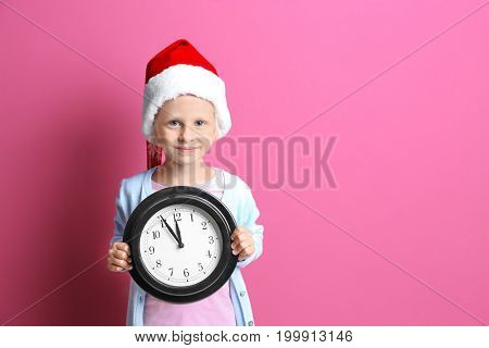 Cute little girl in Santa hat with clock on color background. Christmas countdown concept