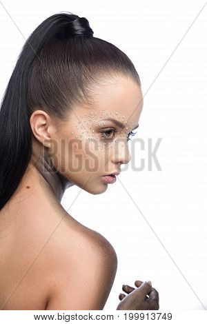 Brunette beautiful woman with crystals on face. Fashion creative black make-up on neck and hands with Swarovski.