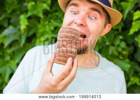 Funny man tourist holds in hand Trdlo or Trdelnik background. Fresh Appetizing Trdlo or Trdelnik - Traditional National Czech Sweet Pastry Dough