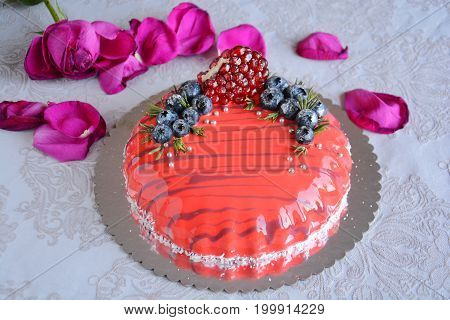 Luxury and beautiful mirror glazed homemade mousse cake decorated with white straps and red fruits with flowers on white background