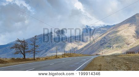 panoramic view of plain with road at root of mountains