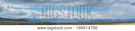 panoramic view of beautiful plain at root of mountains at sunny day with cloudy sky on background