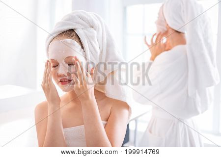I am at home. Delighted young female keeping eyes closed and smiling while setting her mask straight