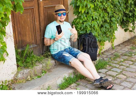 Cheerful man holding and pointing smartphone outdoor.