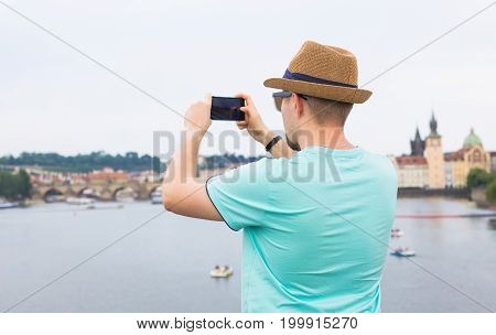 Back view of a young man tourist taking photo with smartphone in front of river and city.