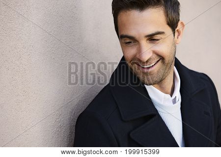 Smiling stubble guy in jacket looking down