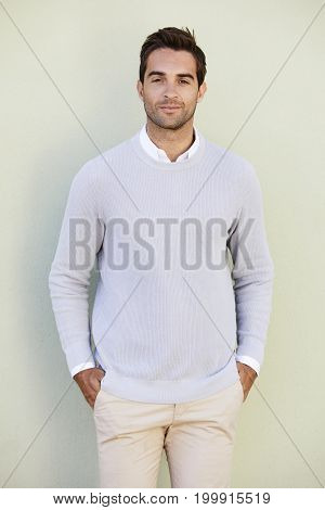 Dude in blue sweater against green background portrait
