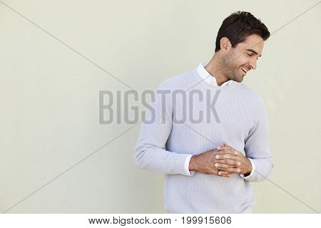 Happy guy in sweater with clasped hands looking away