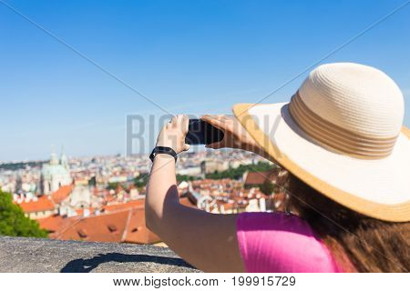 Woman taking pictures with smartphone. Stylish summer traveler woman in hat with camera outdoors in european city, old town Karlovy Vary in the background, Czech Republic, Europe.