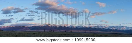panoramic view of plain at root of mountains with cloudy sky on background